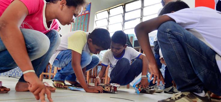 Quatro jovens sentados em volta de um protótipo