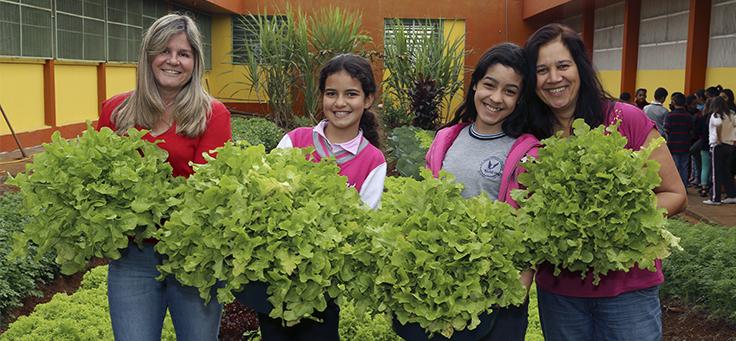 Professoras e crianças cuidando de horta