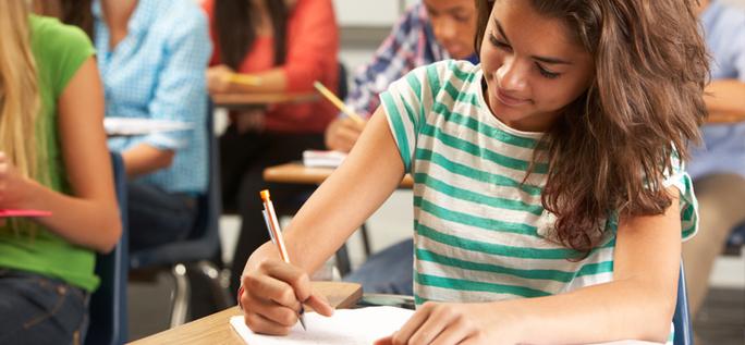 Imagem mostra menina de camiseta listrada branco e verde em uma sala de aula, escrevendo em um caderno.