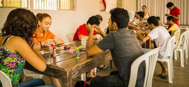 Jovens sentados em volta de mesa trabalhando