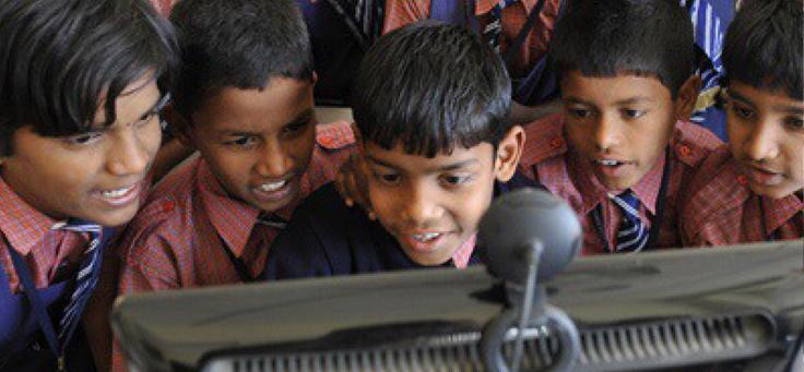 Imagem mostra cinco garotos sorrindo em frente a um computador