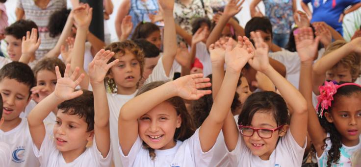 Imagem mostra crianças uniformizadas sorrindo com os braços para cima em movimento