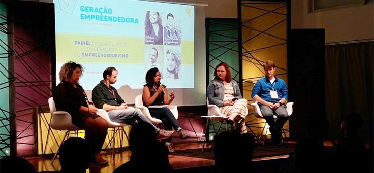 """Imagem mostra pessoas em um painel. No fundo há uma apresentação onde se lê """"Geração Empreendedora""""."""