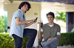 Dois rapazes, um de camisa xadrez e outro de camisa cáqui, olhando para a câmera, com telão ao fundo.