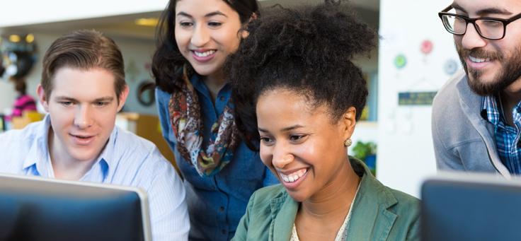 Imagem mostra quatro pessoas sorridentes atrás de um computador