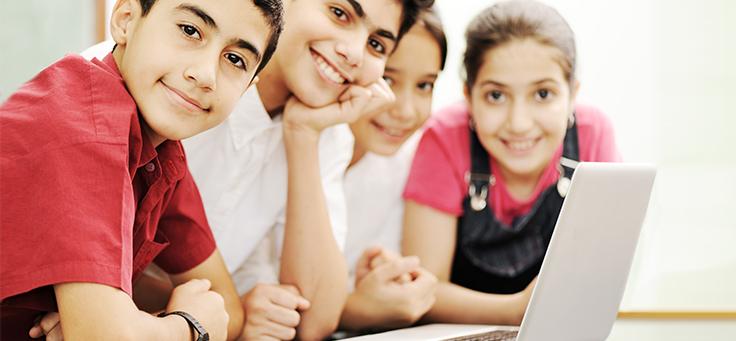 Crianças em frente ao computador olhando para o expectador