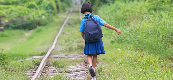 Imagem mostra uma criança caminhando/brincando com uniforme e mochila escolar