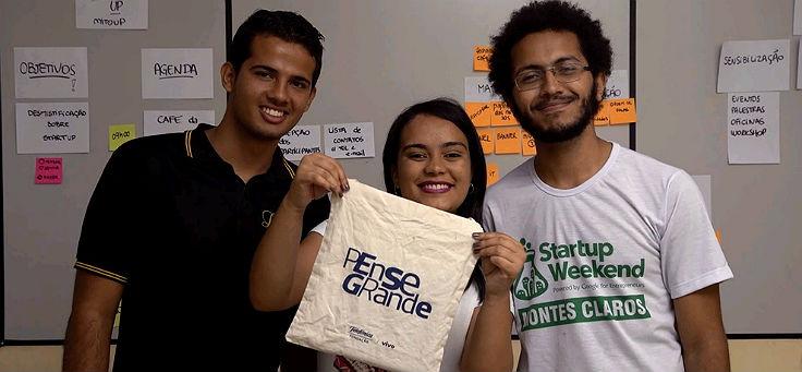 Três jovens empreendedores lado a lado com uma sacola com o logotipo do Pense Grande