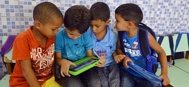 Imagem mostra crianças sentadas em torno de um tablet