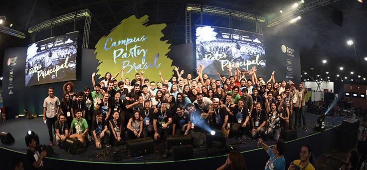 Imagem mostra muitas pessoas reunidas em um palco. Ao fundo se lê Campus Party
