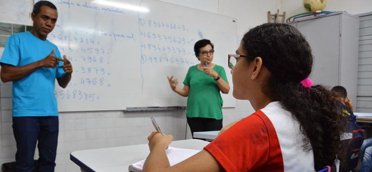 Aluna acompanha explicação de professores em sala de aula