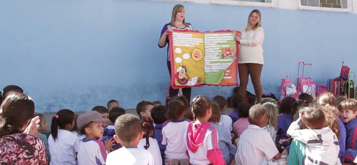 Imagem mostra duas professoras apresentando um livro colorido aos alunos