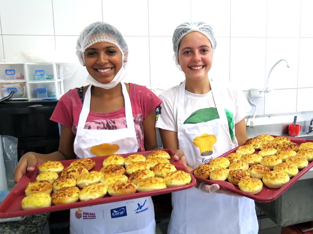 A cozinha industrial aumentou sua capacidade de produção e ainda gera renda extra para a ONG. Duas mulheres mostram bandeijas de pão
