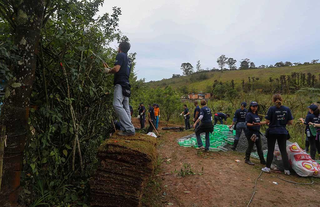 Colabradores trabalham nas instalaçãoes e jardins da ONG Chácara das Flores no Dia dos Voluntários