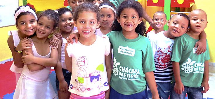 Imagem mostra crianças sorridentes com camisetas escrito Chácara das Flores