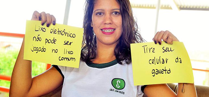 Marísia Maria Costa, é um das criadoras do projeto. Na imagem ela aparece segurando cartazes sobre o lixo eletrônico