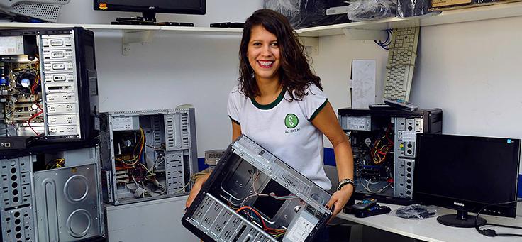 Marísia Maria Costa, é um das criadoras do projeto. Na imagem ela aparece segurando um computador