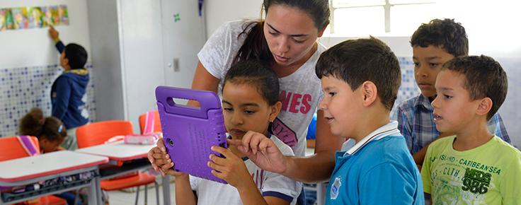 Imagem mostra professora usando tablet azul ao lado de quatro crianças