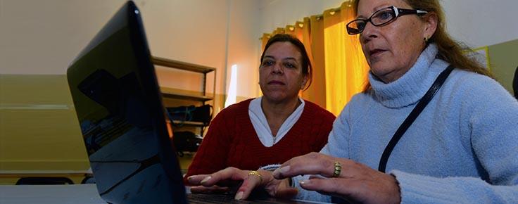 Imagem mostra professora usando computador