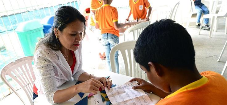 Imagem mostra professora usando camisa branca, sentada, explicando a aluno do projeto Aula Digital