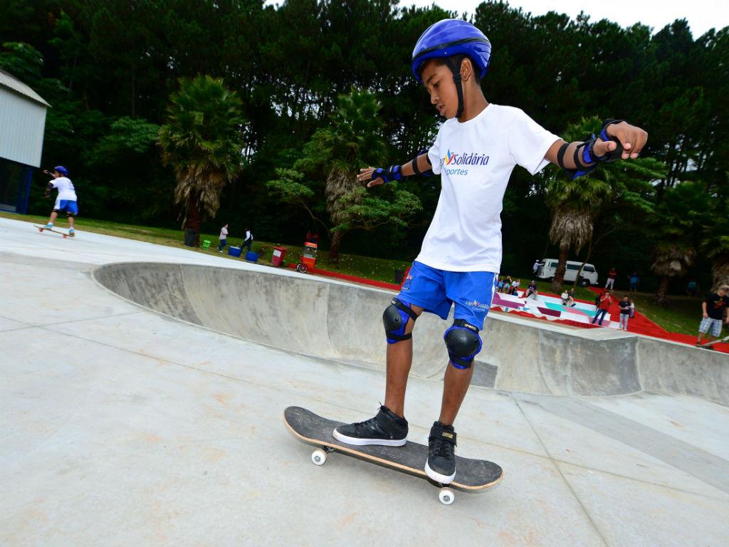 Imagem mostra menino usando capacete andando em um skate no Complexo Educandário no Butatã