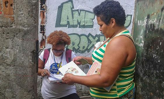 Imagem mostra colaboradora do projeto Aluno Presente falando com mãe de criança