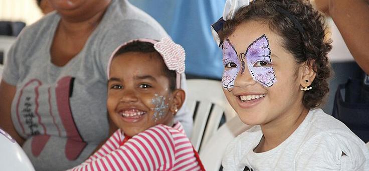 Duas crianças sorrindo. Uma delas está com uma borboleta desenhada no rosto