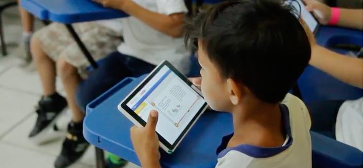 Menino segura tablet sentado em mesa azul. Ao redor dele há outras crianças