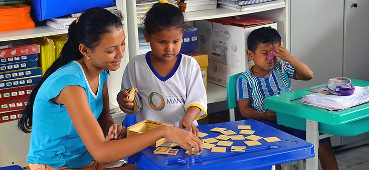 Imagem mostra professora ao lado de aluna brincando com objetos sobre a carteira