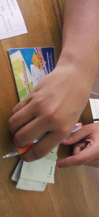 Criança deposita dinheiro em banco educativo em escola na Tailândia