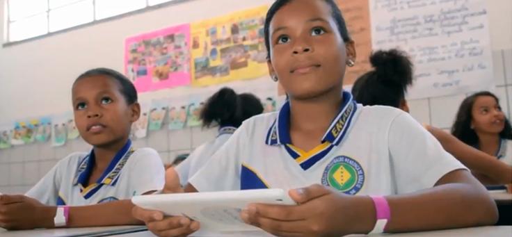 Dois alunos segurando tablets estão sentados em suas mesas usando uniformes. Há outros estudantes ao redor.