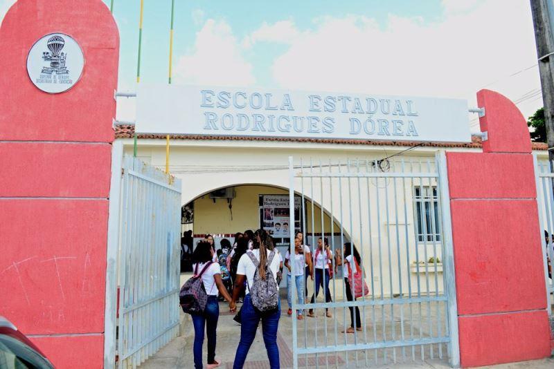 Estudantes com mochilas aparecem entrando na Escola Estadual Rodrigues Dórea, em Aracaju