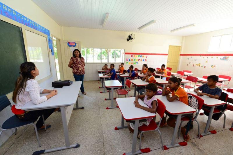 Duas educadoras dão aula na Escola Rural Povoado Cabrita. Uma está sentada, a outra em pé sorrindo