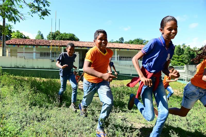 Três estudantes correm pela grama e se divertem
