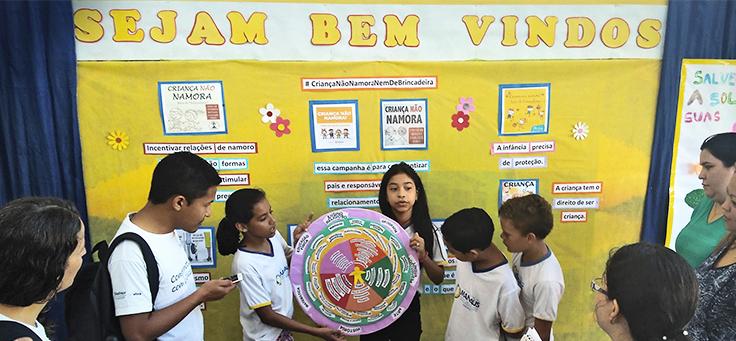 Seis crianças apresentam cartaz em forma de mandala