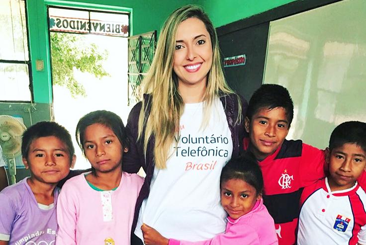 Camila Silva ao lado de crianças peruanas em escola