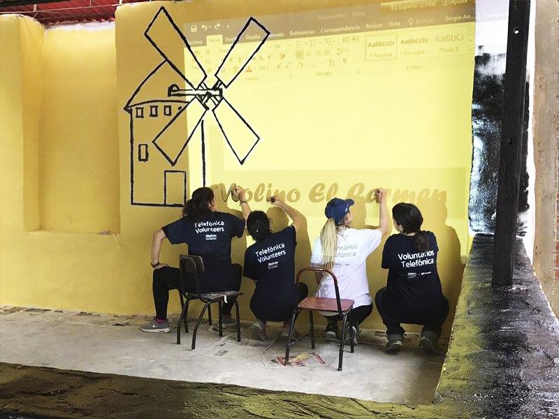 Voluntários pintam parede em Escola Molino de Carmen, no Peru, tem parede pintada com nuvens e arco-íris