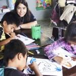 mulher voluntária da Telefônica sentada ao lado de crianças em uma mesa em sala de aula