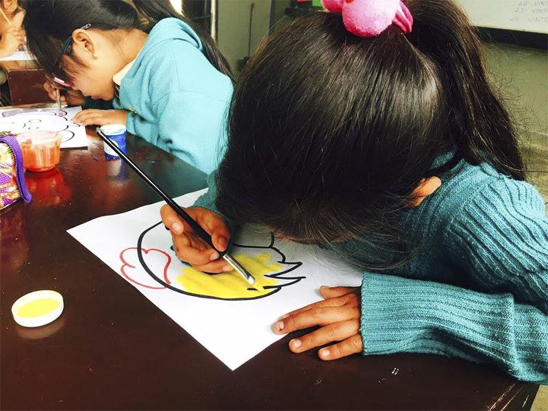 Criança desenha em folha de papel