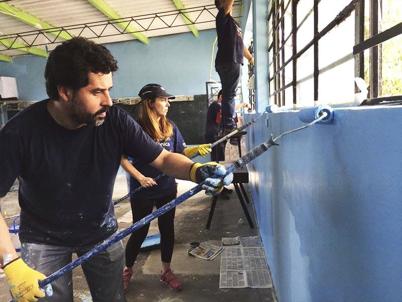 Voluntários pintam parede da escola Molino de Carmen, no Peru