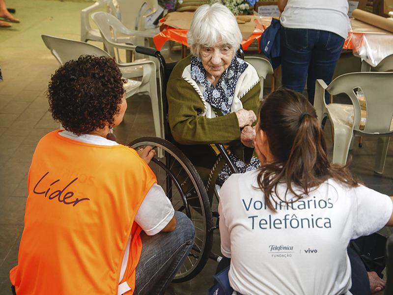 Idosa conversa com duas voluntárias_Dia dos Voluntários
