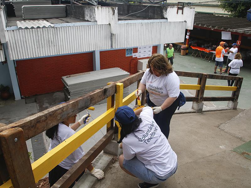 Voluntárias pintam cerca no Nosso Lar_Dia dos Voluntários