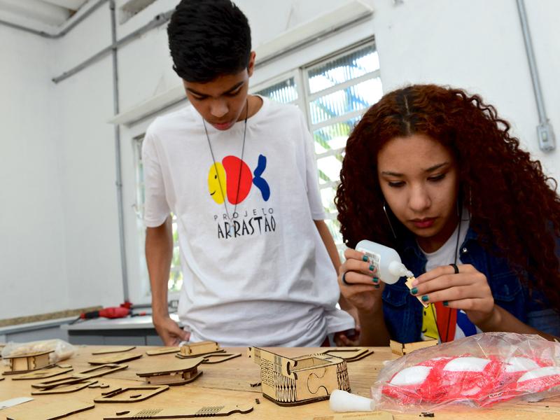 Jovens trabalham em mesa de moldes no Lab Maker Arrastão