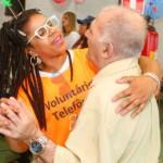 Idoso dança em par com uma voluntária no Dia dos Voluntários