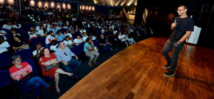 Eduardo Lyra apresenta palestra para plateia em palco