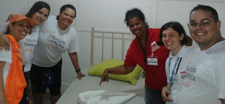 Imagem mostra voluntários em quarto da ASAB arrumando cama