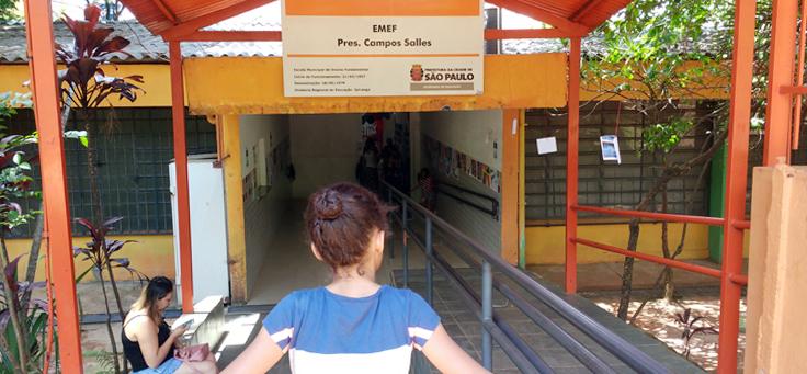 Fachada da escola Campos Salles mostra uma criança olhando para a placa em que está escrito EMEF Campos Salles
