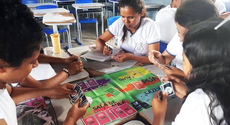 Jovens sentados em mesa com tabuleiro jogam o jogo Se Vira do Pense Grande