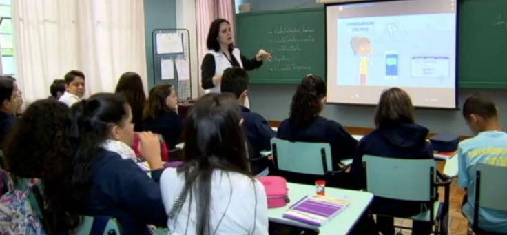 Cerca de 10 alunos sentados em carteiras, de costas, observam projeção em telão dentro da sala, enquanto professora, de pé, explica dinâmica