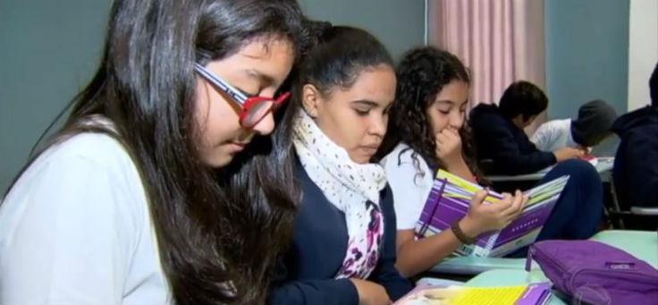 Em sala de aula, três estudantes participam de atividade do Programa Semente, acompanhando o conteúdo pelos livros